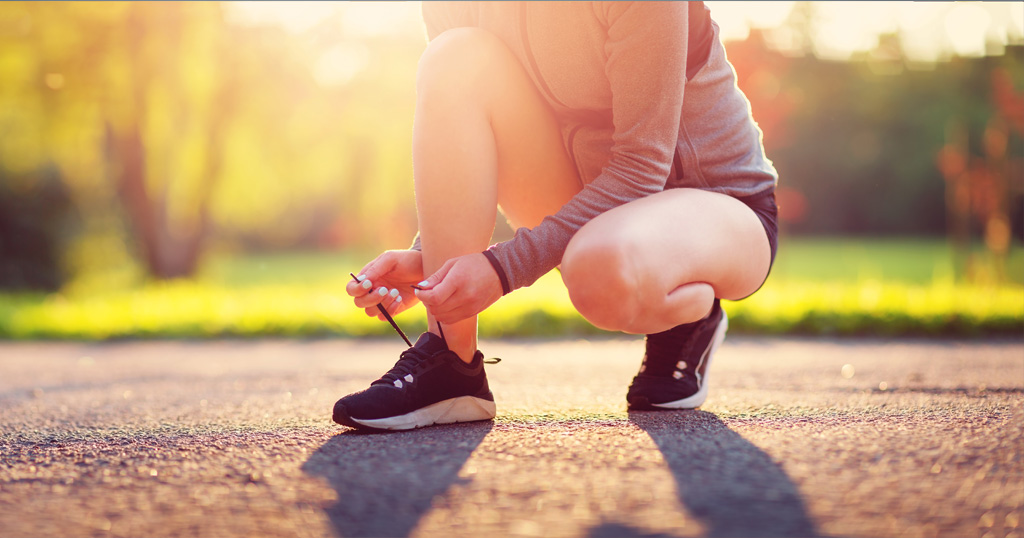 Female runner ties shoes in the sun