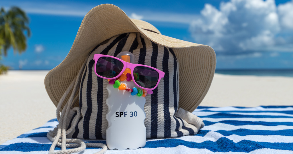 Towel, hat, sunglasses, and SPF lotion on a beach